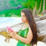 Beautiful teen girl using cellphone on Hawaiian beach, standing next to driftwood