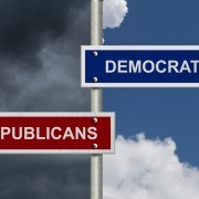 Red and blue street signs with blue and stormy sky with words Republicans and Democrats, Republicans versus Democrats