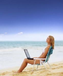 girl on laptop on the beach