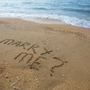 a photo of marriage proposal written on sandy beach
