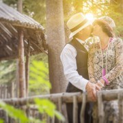 Attractive 1920s Dressed Romantic Couple Kissing on Wooden Bridge.