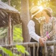 Attractive 1920s Dressed Romantic Couple Kissing on Wooden Bridge.
