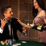 beauty guy flirting with a girl who pours champagne at the poker table in casino