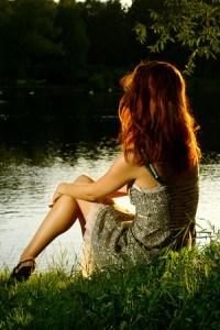Woman sitting at lake's edge