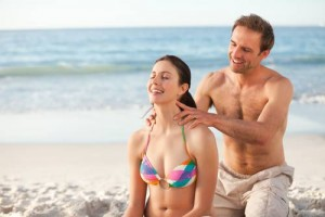 Man giving woman a massage on the beach