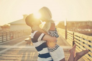 Couple embracing during sunset on pier.