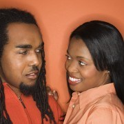 African-American mid-adult couple wearing orange clothing on orange background.