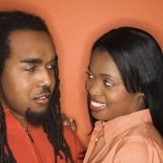African-American mid-adult couple wearing orange clothing on orange background.