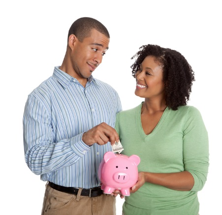 Happy couple feeding a piggy bank
