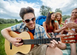 travel, tourism, hike, leisure and people concept - happy man with friends playing guitar at camping