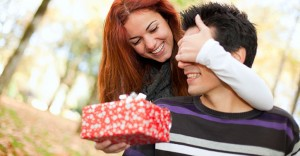 Woman surprising man with a gift