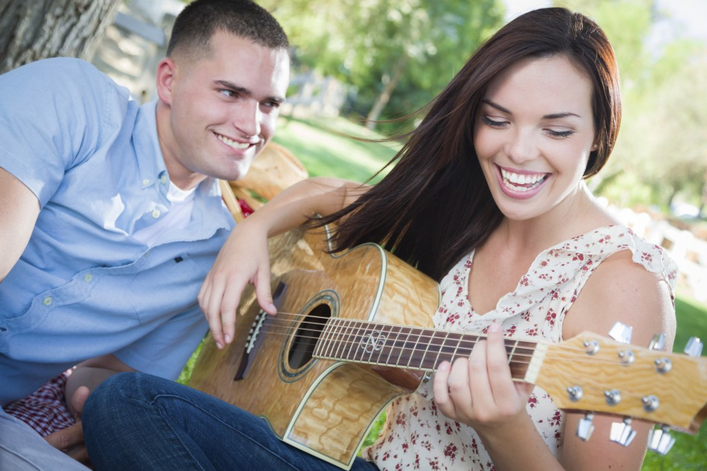 Happy woman playing guitar