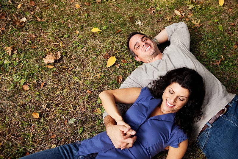 Couple snuggling on a lawn