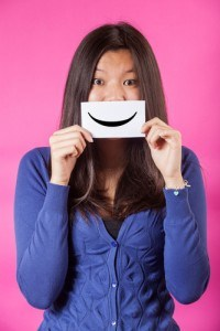 Woman holding smiling emoticon