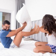 Funny couple fighting with pillows in bed