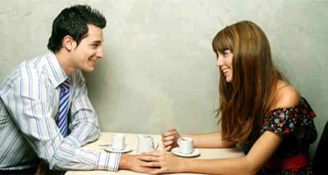 Couple touching and drinking coffee