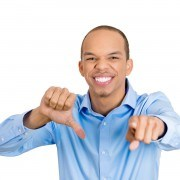 Closeup portrait sarcastic young man showing thumbs down sign, pointing at you, happy that someone made mistake, lost, failed isolated white background. Negative emotion, facial expression feelings