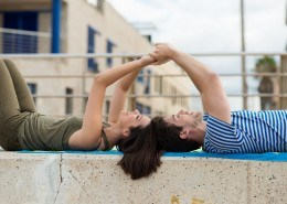 Couple lying relaxing on a cement wall against a white railing in an urban environment holding hands and laughing with enjoyment