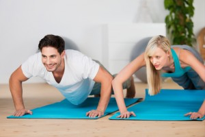 Young couple doing press-ups in a gym