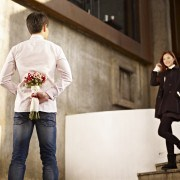 asian young man waiting by the steps with flowers behind back for his girlfriend.