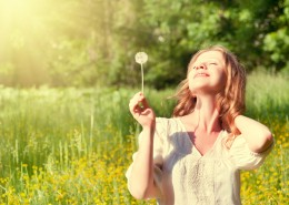 beautiful girl with dandelion enjoying the summer sun outdoors in the park