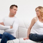 Young caucasian couple sulking after conversation sitting on sofa at home