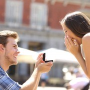 Proposal in the street with a man asking marry to his happy girlfriend