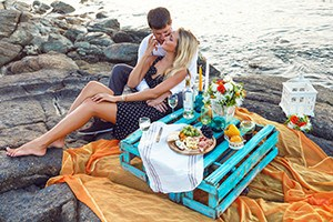 Couple having picnic beside the ocean.