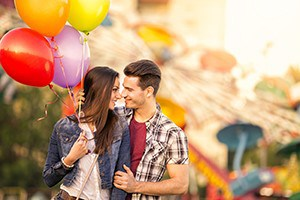 Romantic couple in the amusement park holding balloons.