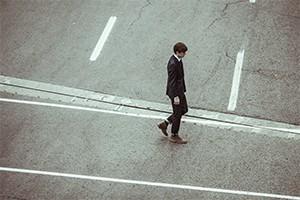 Man walking down empty street alone.