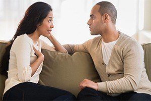 Couple sitting on couch having a serious talk.