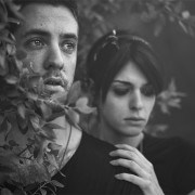 Black and white photo of couple standing in bushes, looking hopelessly into the distance.