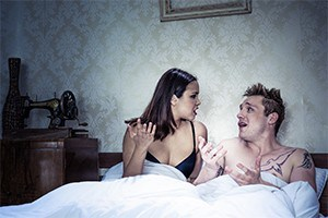 Couple arguing in bed.
