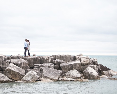 Couple standing on rocks over water.