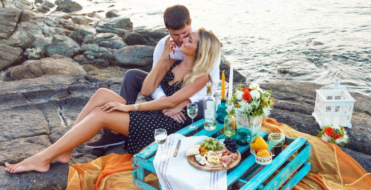 young couple having a picnic on the beach