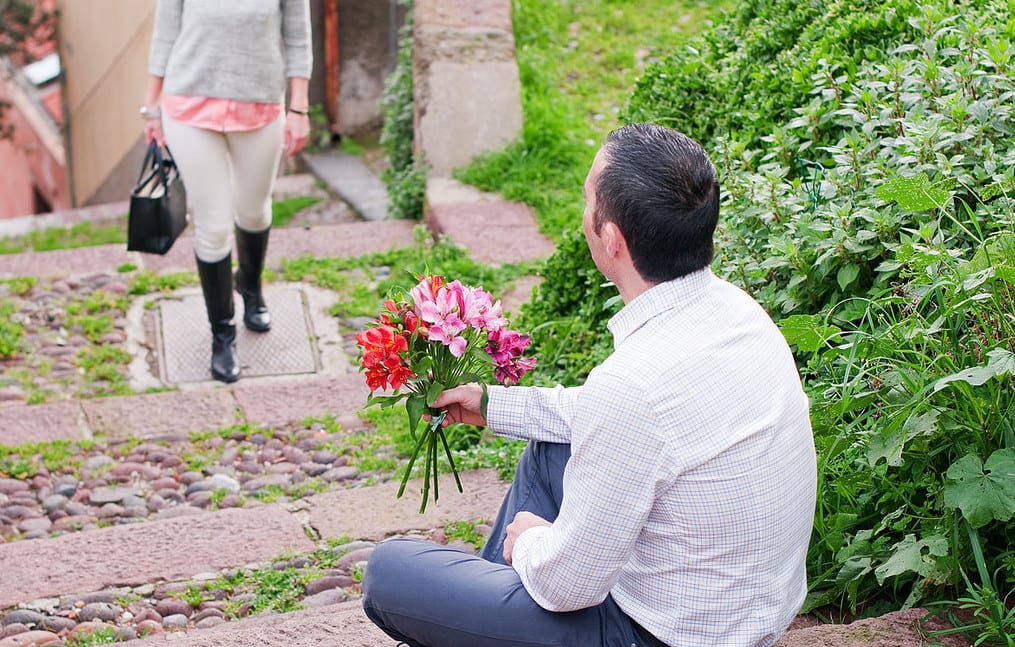 man waiting on steps for woman with flowers