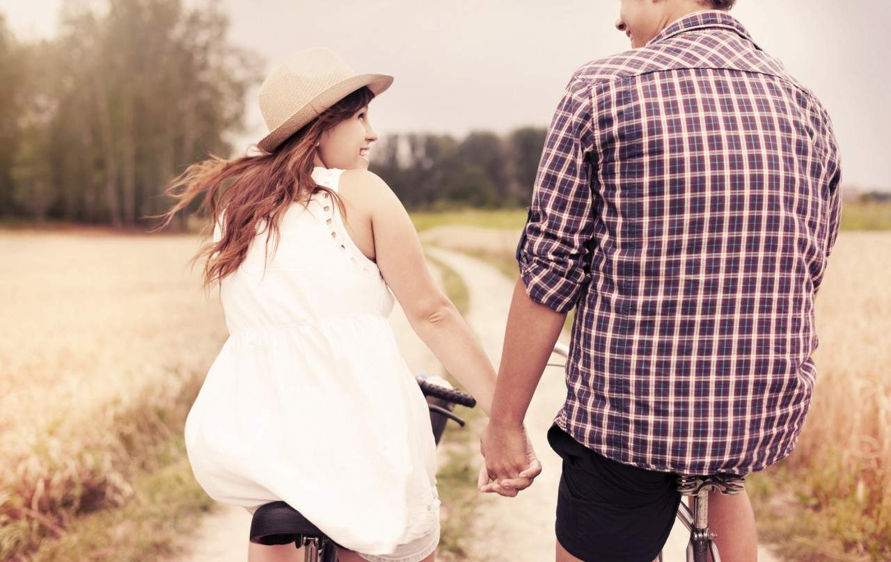 couple holding hands on a bike ride