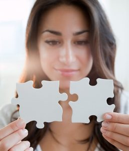 young woman holding two puzzle pieces in front of her face.