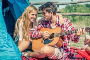 man plays guitar for woman