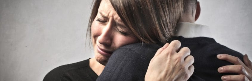Sad wife hugs her husband