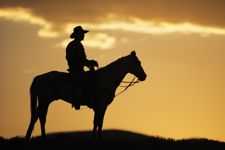 cowboy riding into sunset